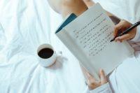 一个女孩坐在床上喝着咖啡,在笔记本上写字