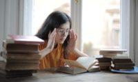 一个女孩开着书坐着