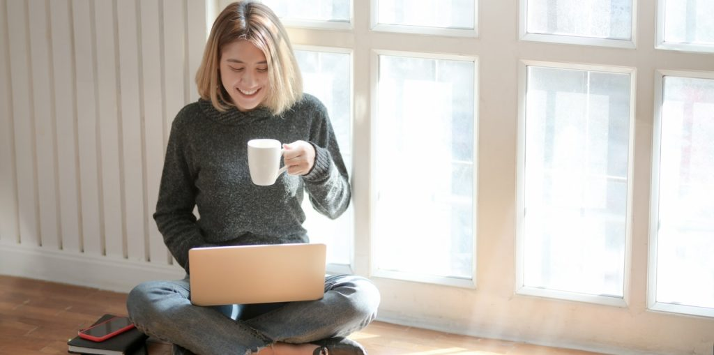 a girl is sitting with a laptop and a cup of coffe in her hands